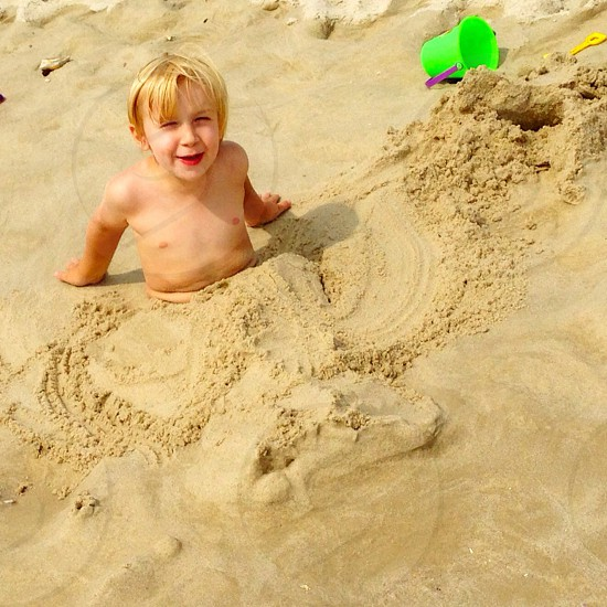 Burying himself in the sand! photo