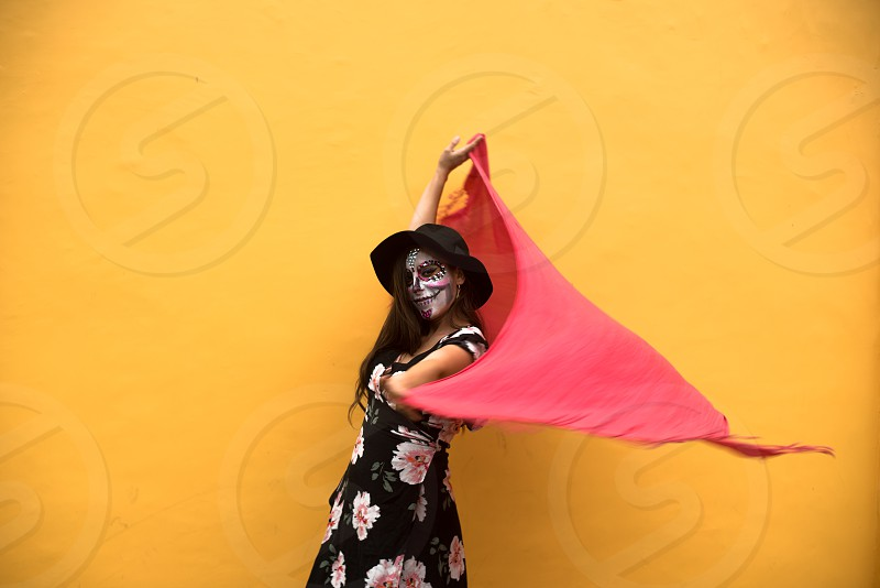 Young woman painted for Day of the Dead with a colorful background  photo