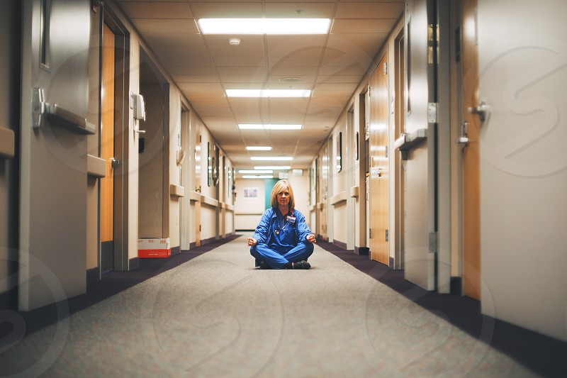 nurse in blue scrubs sitting in hallway photo