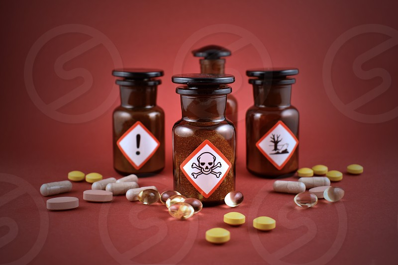 Vial of poison. Vial with warning pictogram. Laboratory accessories. Vials on a red background. Brown glass containers. Brown chemical glass photo