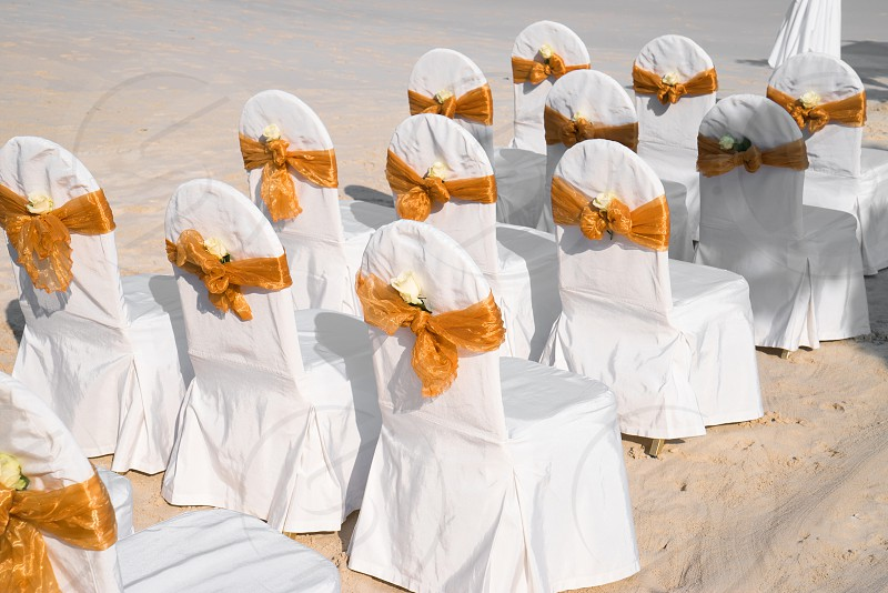Beach wedding venue setting with spandex white cover chairs gold organza sash with cone of roses petal. photo