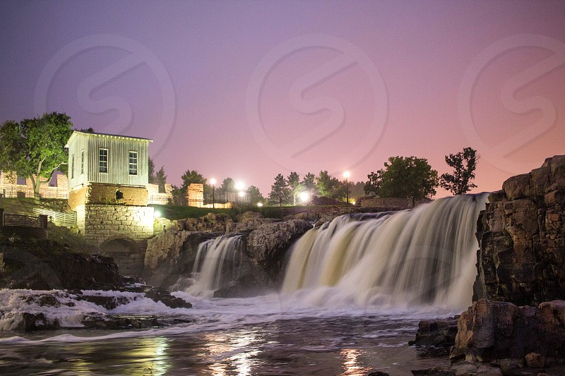 white concrete house lighted by halogen lights near waterfall under sunset landscape photography photo