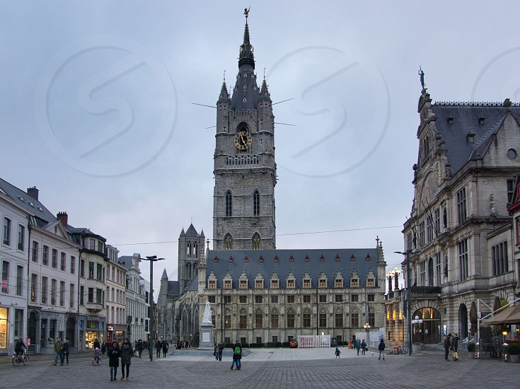 The belfry of Ghent is a 95 meter high tower in the centre of the Belgian city of Ghent. It is part of a row of towers together with the St. Nicholas Church and the Saint Bavo Cathedral. Against the Belfry is the Ghent Cloth hall. This picture was taken between the cathedral and the Belfry.  photo