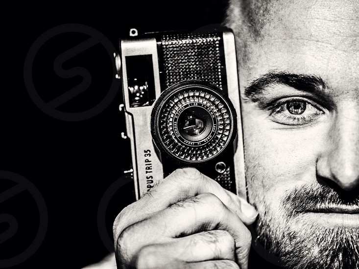 Close up of a man with a beard holding a retro Olympus Trip camera next to half his head in black and white grain finish photo