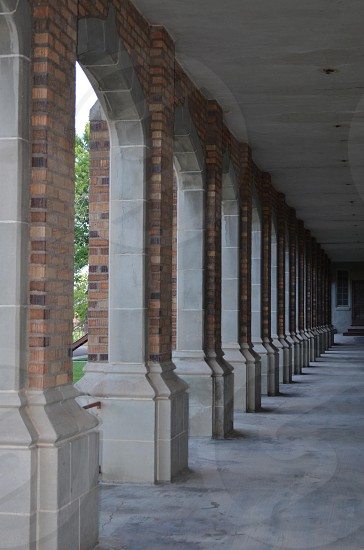 brick and tan stone arched outdoor building walkway photo