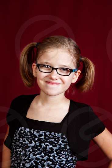 Studio portrait of a young girl on a red background.  She has a confident closed mouth smile and is wearing glasses and ponytails. photo