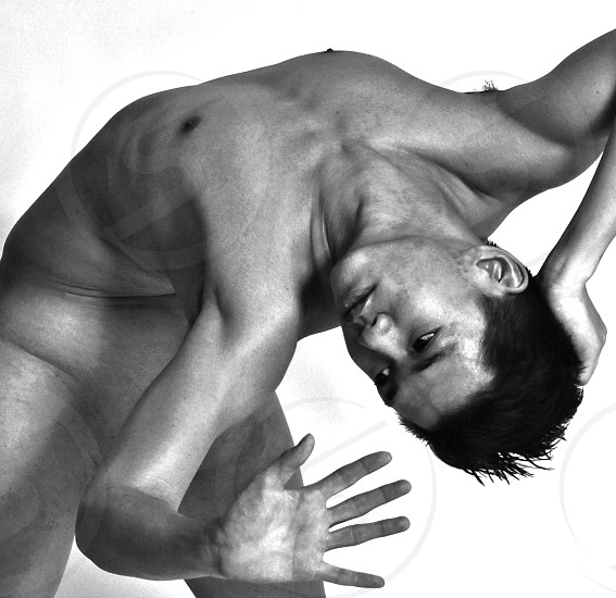 grayscale photography of naked man bending his back photo