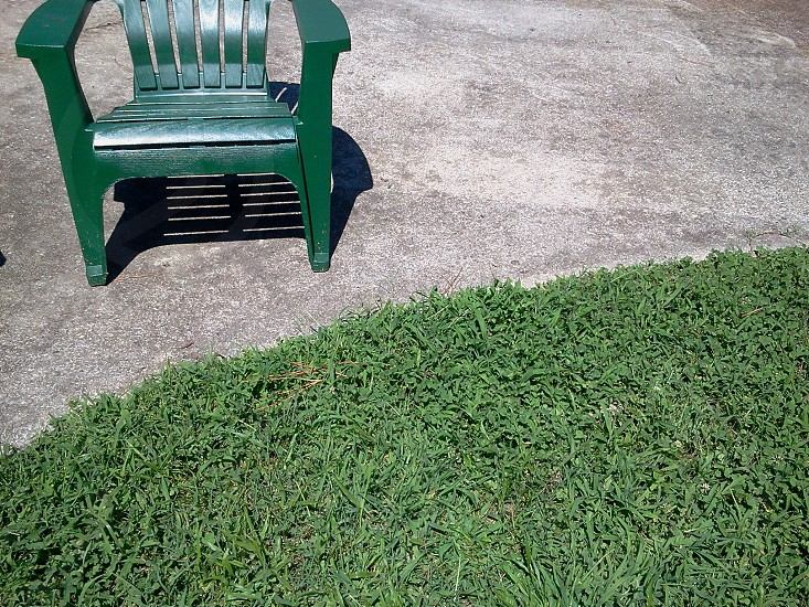 green monobloc chair near green grass photo
