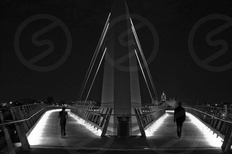 two people walking on the bridge photo