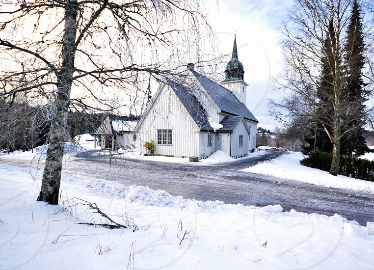 white painted chapel with gray roof on snow covered field photo