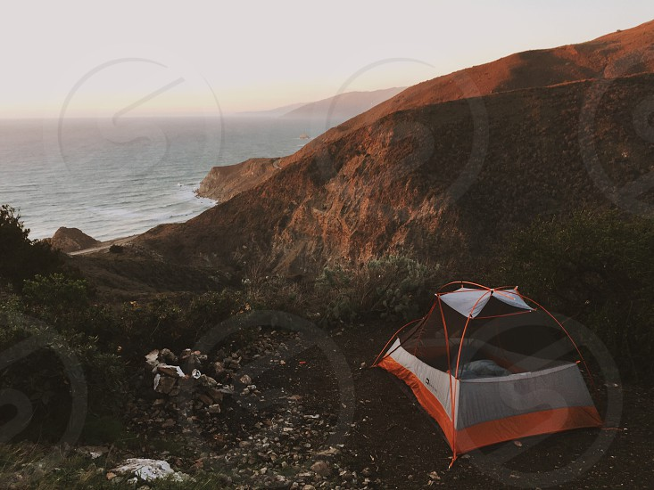 gray and orange tent on mountain beside the sea photo
