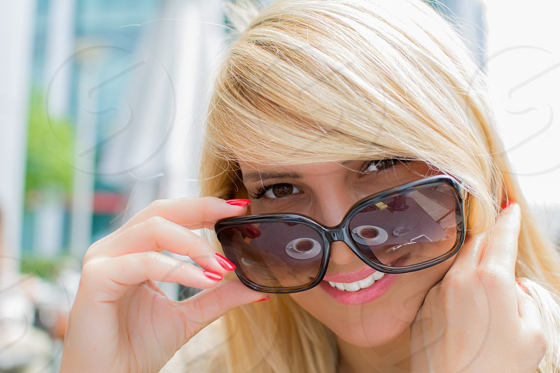Beautiful woman with blond hair black glasses and white teeth smiling in the restaurant photo