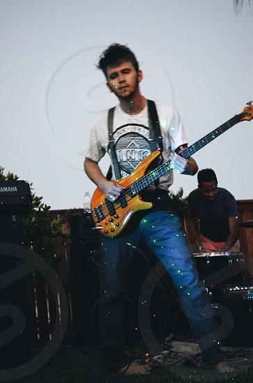 man playing electric bass guitar photo