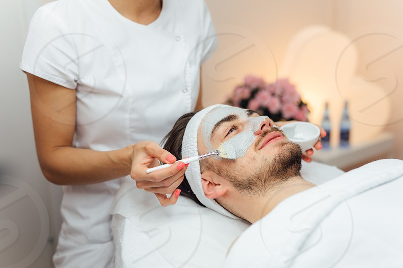 Unshaven man having cosmetic mask care in spa salon side top view - Image photo