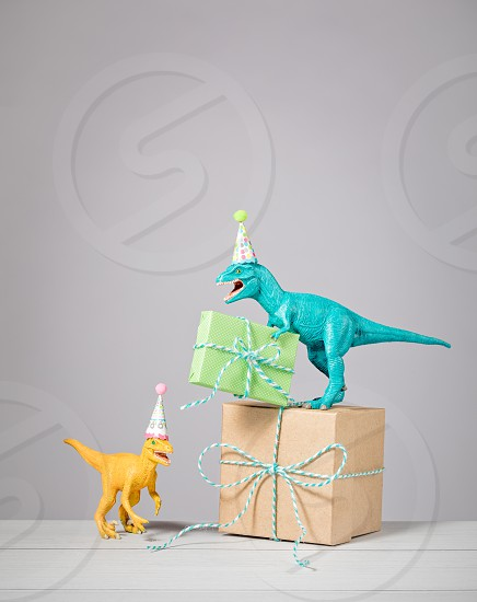 Two dinosaurs with birthday hats and gifts on a light grey background. photo