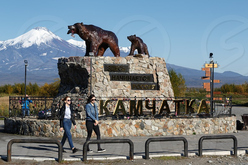 "YELIZOVO CITY KAMCHATKA PENINSULA RUSSIA - SEP 24 2017: Sculpture composition of Kamchatka brown bear family ""She-bear with teddy bear"" inscription: ""Here begins Russia. Kamchatka"" on background of Avacha Volcano. photo"