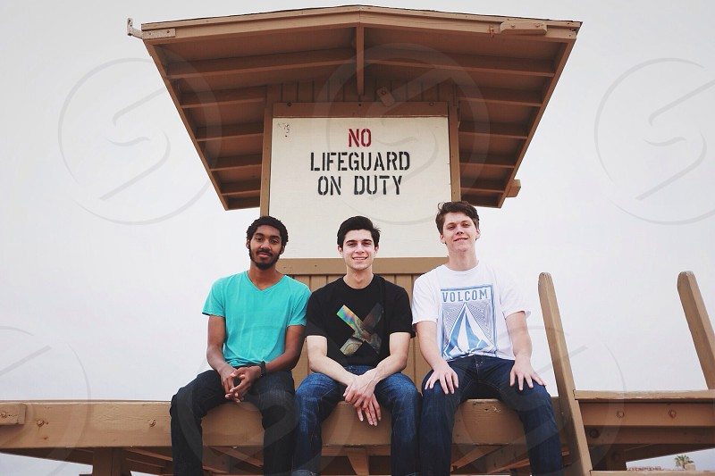 3 person sitting on brown wooden house photo