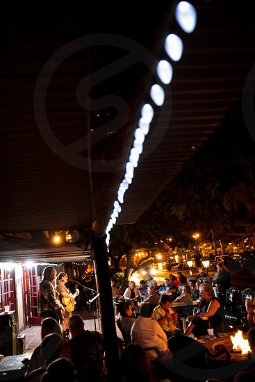 Two young people sing and play guitar for a small crowd at their gig / performance / show outside at night. photo