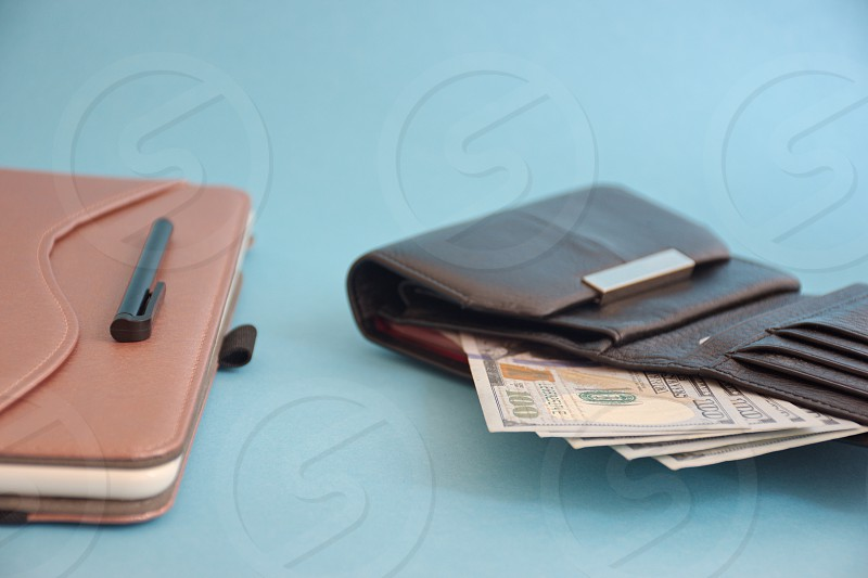 Black wallet with dollar banknotes and tablet against the blue background photo