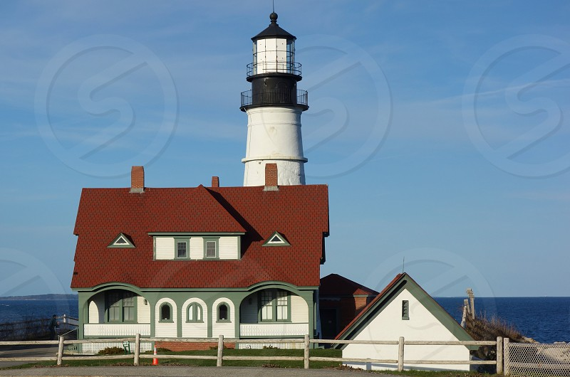 brown and white house in front of white and black lighthouse near body of water during daytime photo