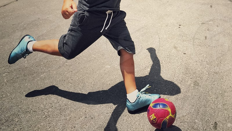 man wearing black shorts and blue cleats ready to kick a red and blue ball on cemetn photo