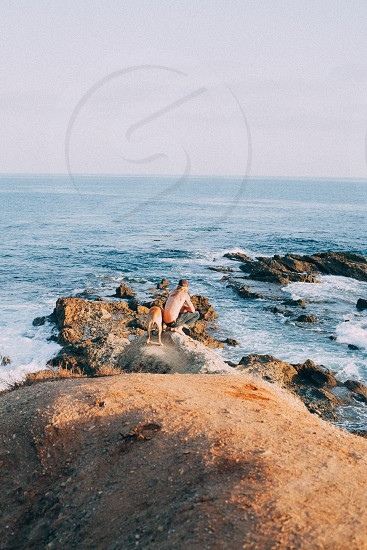 man sitting on the rock near the dog in the shore rock photo