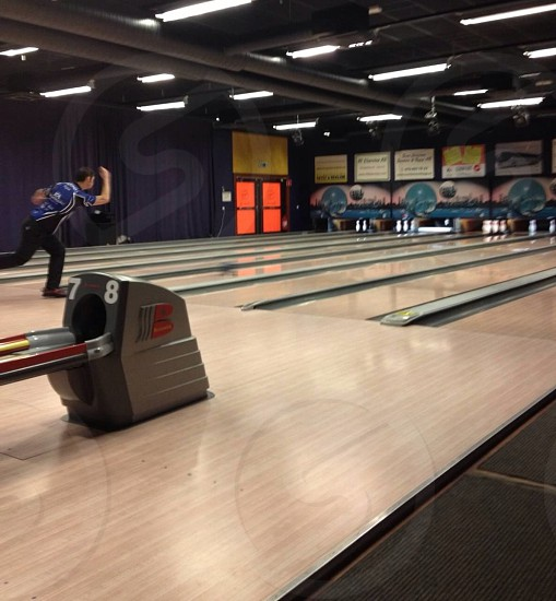 man in blue and white t-shirt and black pants playing bowling photo