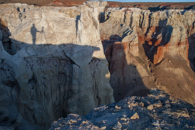 Shadow of photographer on ledge above colorful desert canyon photo