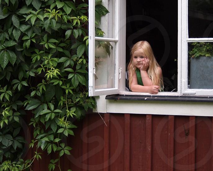 girl standing near white window pane photo