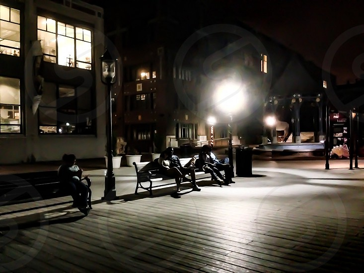 People sitting on bench at night photo