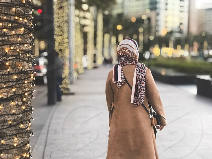 Portrait  millenial  portrait without a face  scarf  hijabi  lifestyle  downtown  walking  people from the back  girl  woman  empowered  street  lights  bokeh  holiday  christmas  photo