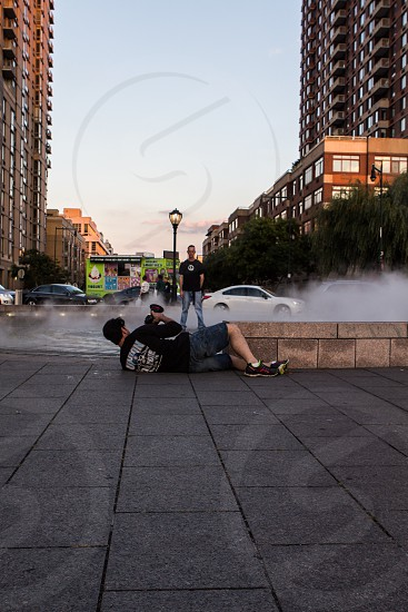 man taking a photo while lying on concrete photo