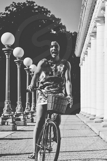 woman in tank dress riding bicycle on pathway beside post lamps in grayscale photography photo