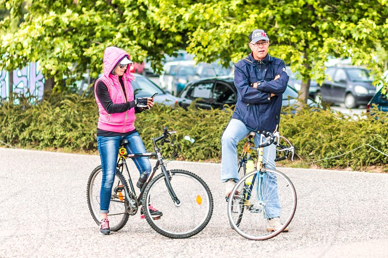 Couple Riding Bikes Outdoor And Checking Mobile Phone photo