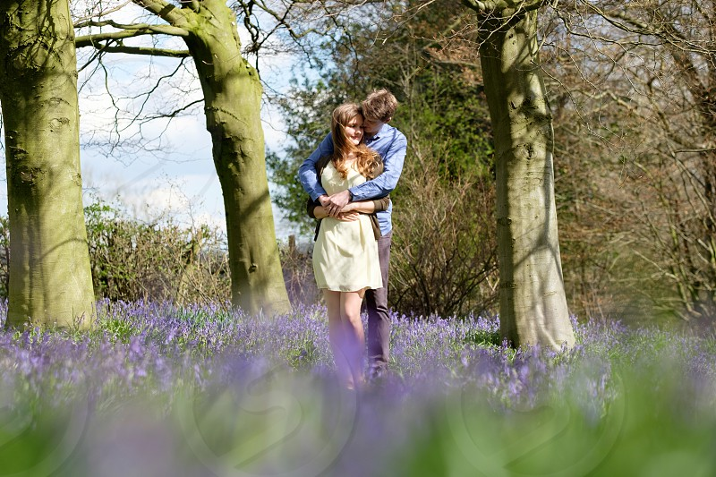Couple cuddling in the woods in the spring  with purple blue bell flowers she is wearing a yellow dress and brown cardigan and he is wearing a blue shirt and great trousers. The photo is taken in a landscape composition with copy space around the couple. photo