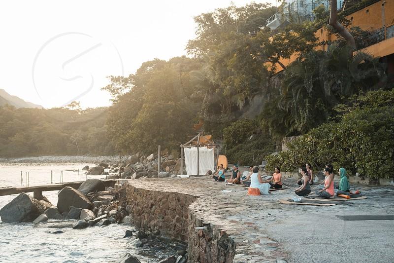 Group of multiple adults meditating outdoors. Yoga retreat Puerto Vallarta - Mismaloya Mexico photo