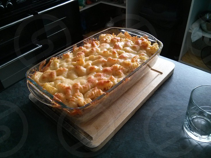 Tuna pasta bake placed on a chopping board at the end of a breakfast bar unit photo