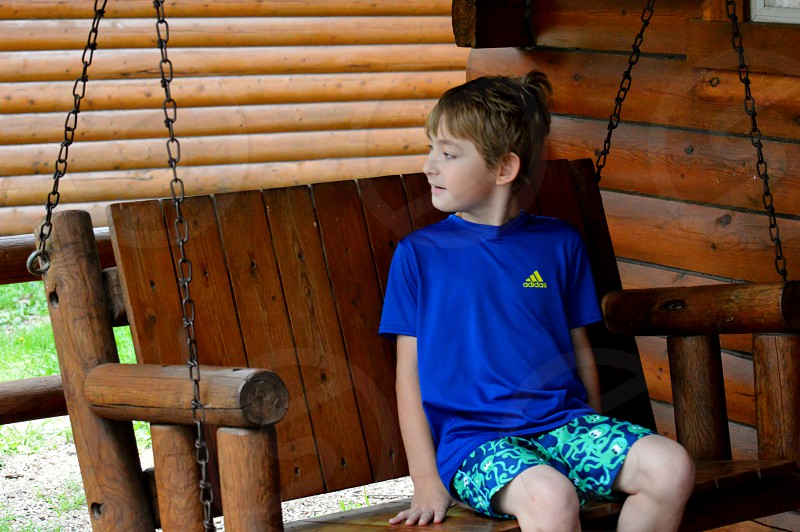 boy in blue adidas round neck short sleeved tee sitting on a brown wooden swing bench photo