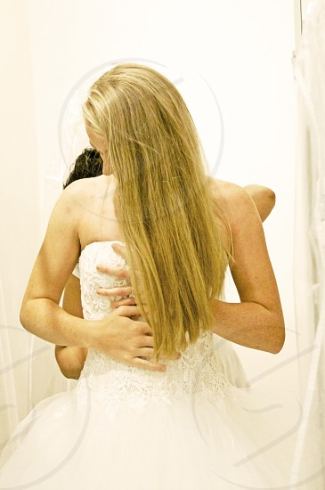 young lady trying on wedding dress photo