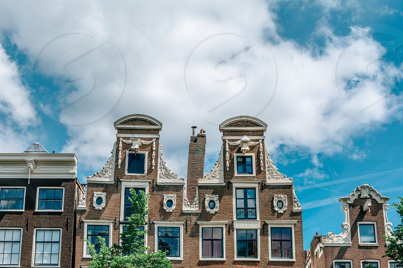 brown and white concrete high story house over blue and white cloudy sky during daytime photo