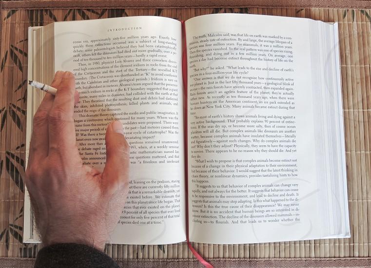 man smoking reading a book photo