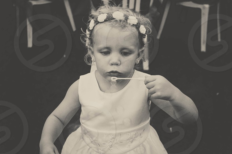 girl in white tank dress floral crown headband blowing bubbles photo