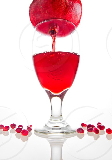 Conceptual shot of pomegranate juice pouring from the fruit photo