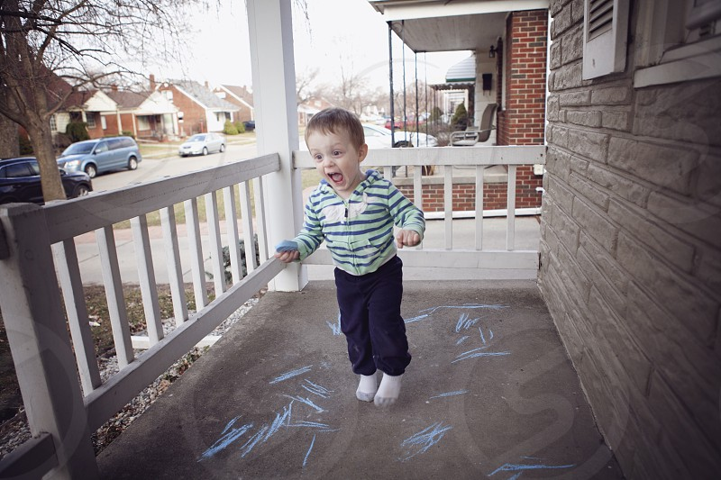 laughing toddler in white and green striped sweater in porch photo