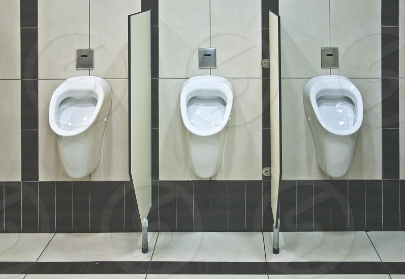Three Men's toilet with urinals photo