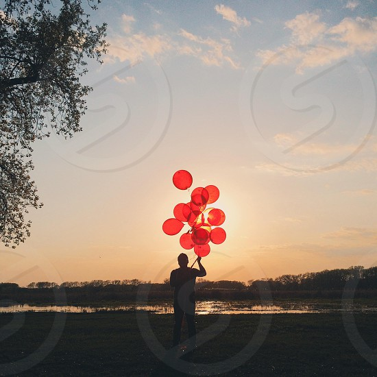 man holding red balloons by green tree photo