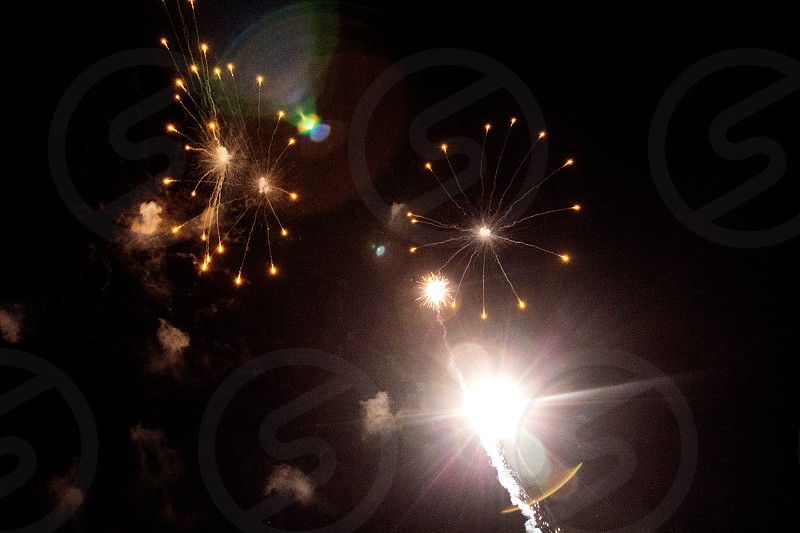 White fireworks on black with lens flare photo