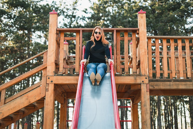 Young happy woman enjoying on the slide in the public playground photo