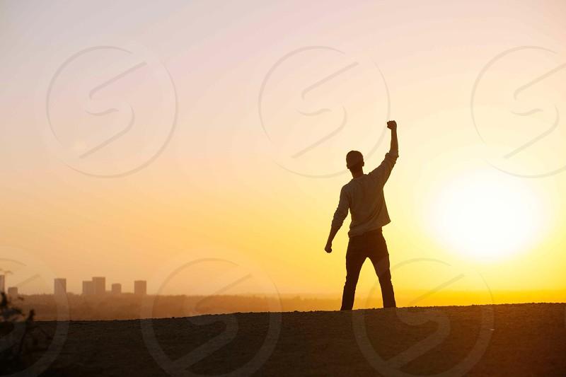 man raising hand while standing photography photo