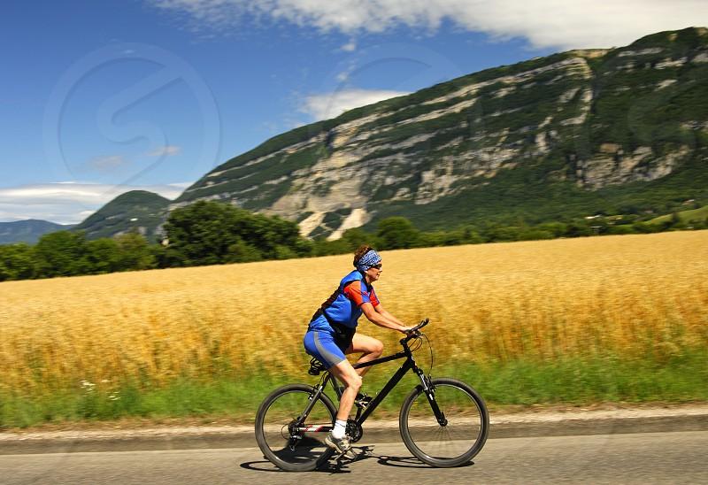 Young woman biking uphill past a colza field photo